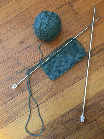 green yarn ball, silver aluminum knitting needles, and a matching knit project on a wooden surface