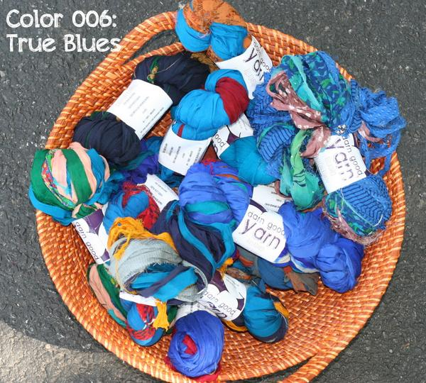 Multiple skeins of blue and multicolored yarn sitting in a large wicker basket on a black pavement surface