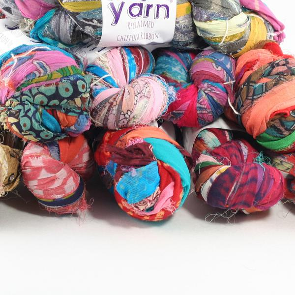 Stack of multiple skeins of multicolored and patterned chiffon ribbon yarn stacked on a white background