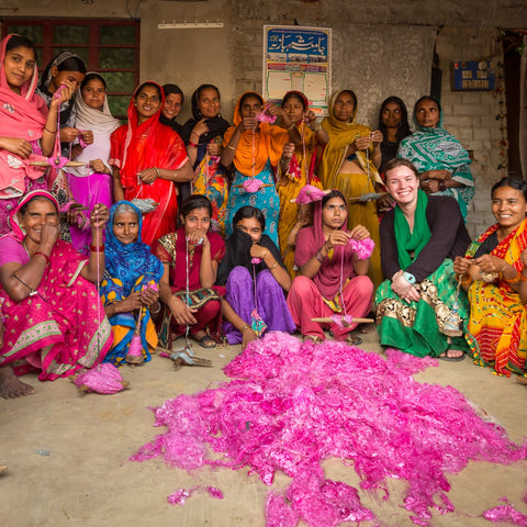 A group of women are sitting in a dirt-floor room. They are all wearing colorful saris and are sitting behind a large pile of magenta banana pulp that will soon be spun into banana fiber yarn. They are all smiling at the camera
