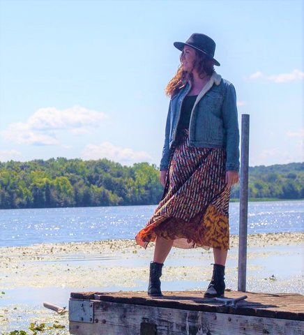 Woman wearing a sari wrap skirt, winter jacket, hat and boots, standing on a dock in front of a body of water