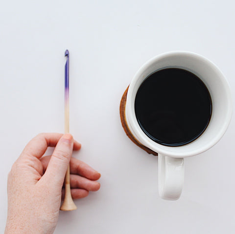 Woman's hand holding a wooden ombre crochet hook and a white mug of coffee on a white background