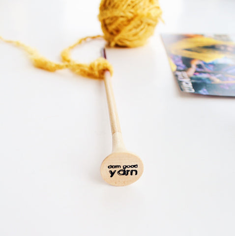 Wooden crochet hook with 'darn good yarn' engraving with a yellow ball of yarn on a white background