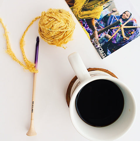 Wooden crochet hook, yellow ball of yarn, white mug of coffee, and a crochet pattern sitting on a white surface