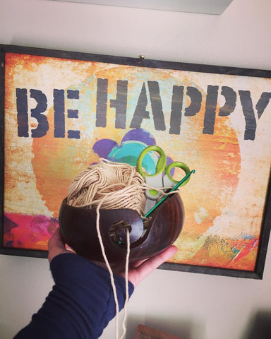 Woman's hand holding out a Wooden yarn bowl filled with yarn, scissors, and a crochet hook, in front of a poster that reads 'Be Happy'
