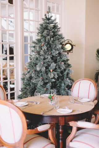 Large Christmas tree standing in a dining room with a decorated circular table and four chairs