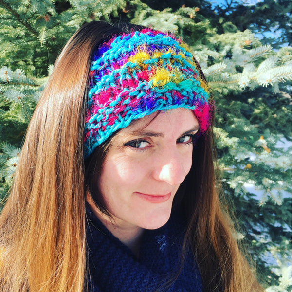 Woman wearing Darn Cute Earwarmer in front of a snowy pine tree
