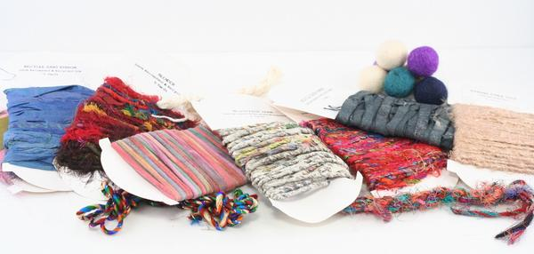 Multiple white cards full of different colors and textures of yarn samples strewn on a white surface
