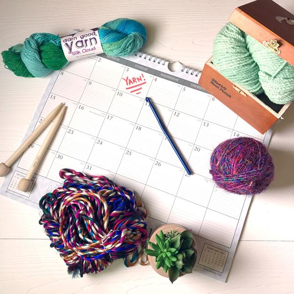 3 skeins of yarn, a potted house plant, a pencil, a pair of wooden knitting needles, and a cardboard box full of yarn sitting on a large desk calendar on a white desktop