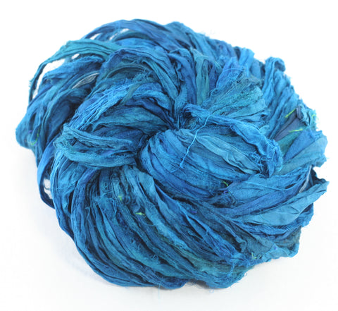 Sari Silk Ribbon yarn ball in blue sitting on a white background