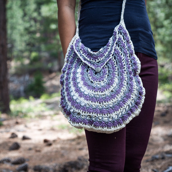 Woman wearing crochet bag standing in the woods