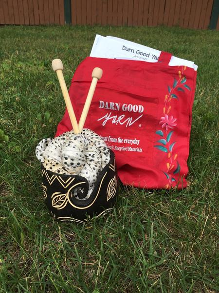 Red Darn Good Yarn Tote Bag sitting in grass next to a wooden yarn bowl holding a black and white ball of yarn in front of a wooden fence