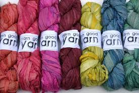7 skeins of yarn in ROYGBV colors all with white Darn Good Yarn labels arranged on a white background