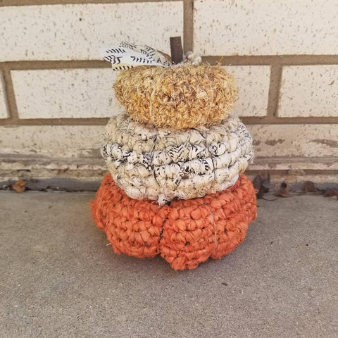 3 stacked crochet pumpkins sitting on a concrete surface in front of a brick wall