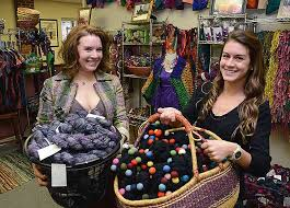 Two women holding large baskets full of multicolored yarn, standing in a store filled with colorful clothing