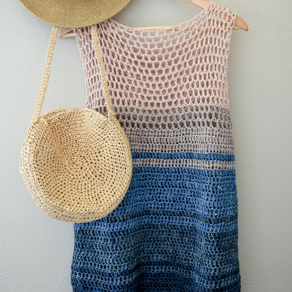 Easy Breezy Top hanging on a wooden hanger on a white wall with a straw hat and purse