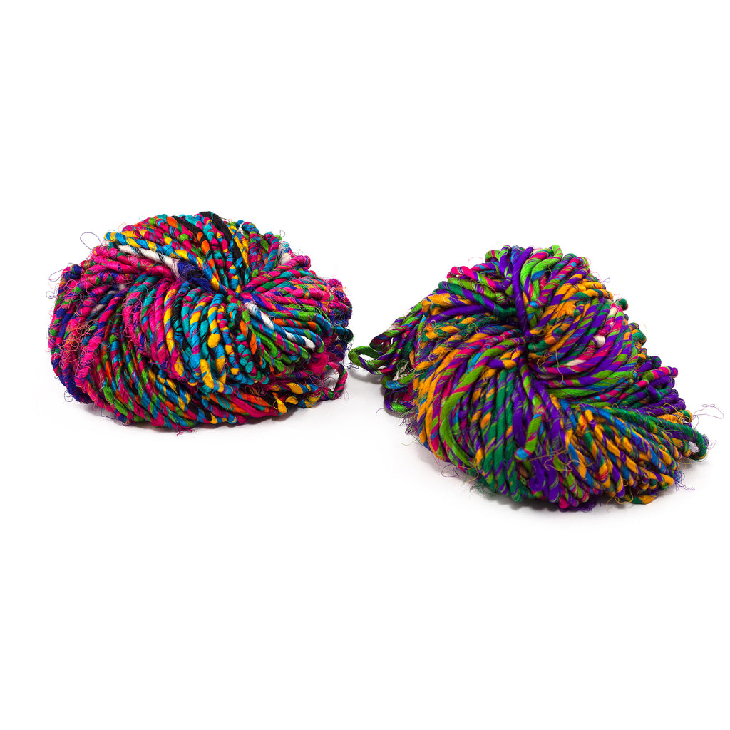 Two balls of multicolored Firecracker Recycled Resolution yarn on a white background