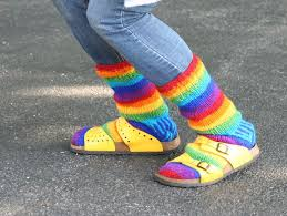 Closeup of woman's legs wearing blue jeans, rainbow wool socks, and yellow sandals