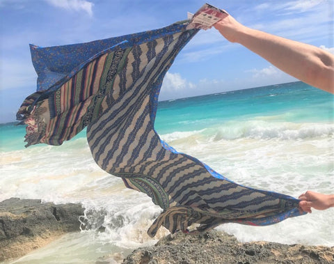 sari wrap skirt held by woman's hands and blowing in the wind over an incoming ocean tide