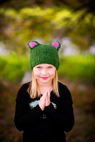 Little girl wearing a black sweater and a green knit beanie
