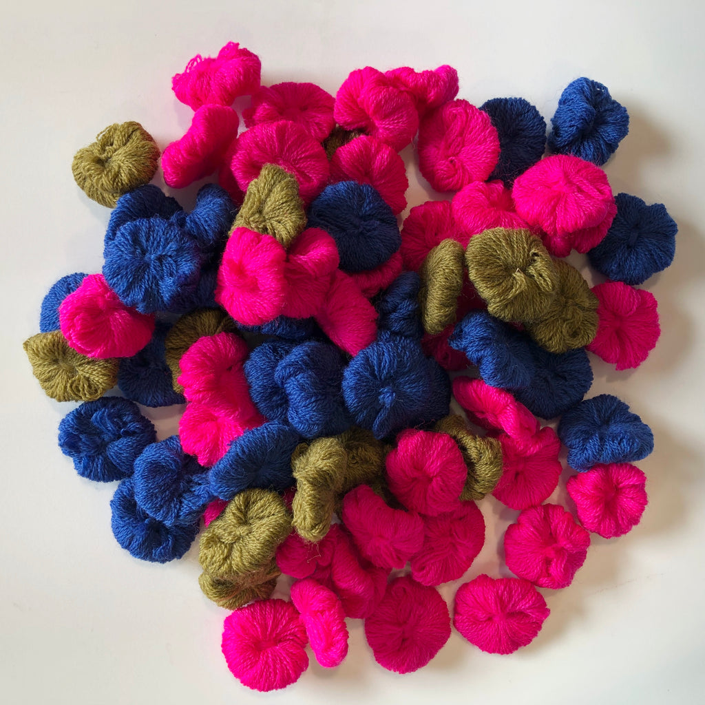 pile of small bundles of wool thread in pink, blue, and green on a white background
