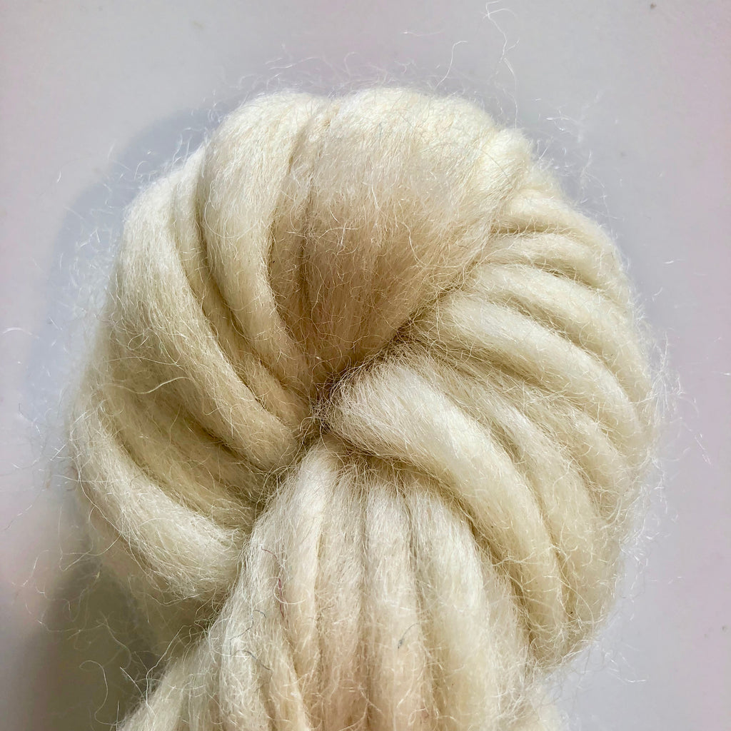 Close up of Variegated Thick and Thin Wool Yarn skein in Natural Undyed color way on a white background
