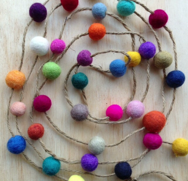 Multicolored felt balls strung on a long strand of hemp yarn, all laid on a wooden surface