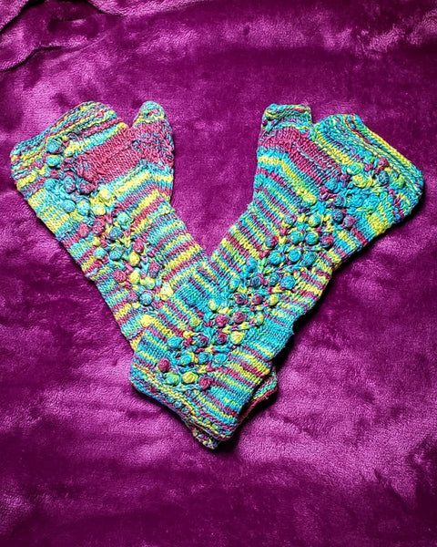Juicy Fruit fingerless mittens sitting on a purple fuzzy blanket