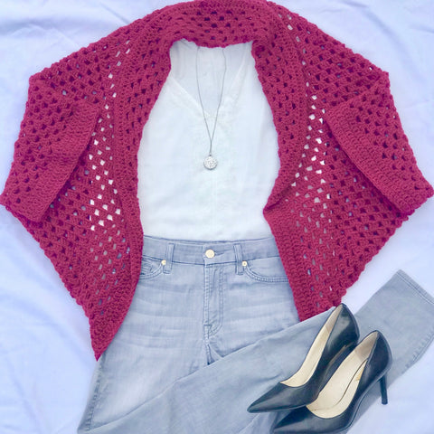 Flat lay image of a pink granny square cardi, a white tee, gray jeans, a silver pendant necklace, and black pumps all sitting on a white surface