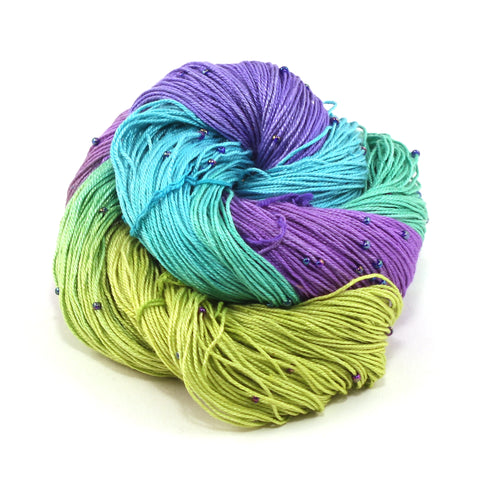 Hand Beaded Silk yarn ball in blue, purple, and green on a white background