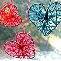 3 wire hearts wrapped in red and blue yarn hanging in front of a clear window