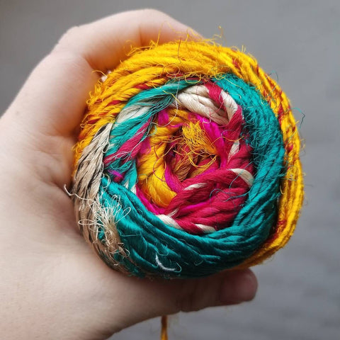 Woman's left hand holding a ball of multicolored recycled Silk yarn