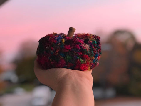 Woman's hand holding out a crochet pumpkin