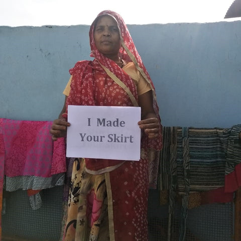 An Indian woman, wearing a red and yellow sari, is standing in front of a grey wall. She is holding a white sign that says 'I Made Your Skirt'.