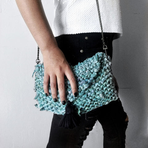 Close up of woman wearing tasseled Sari Silk Clutch Knit bag with black jeans and standing in front of a white background
