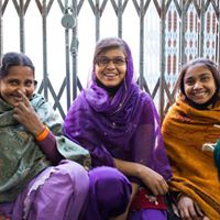 3 women wearing saris sitting in front of an iron fence, smiling