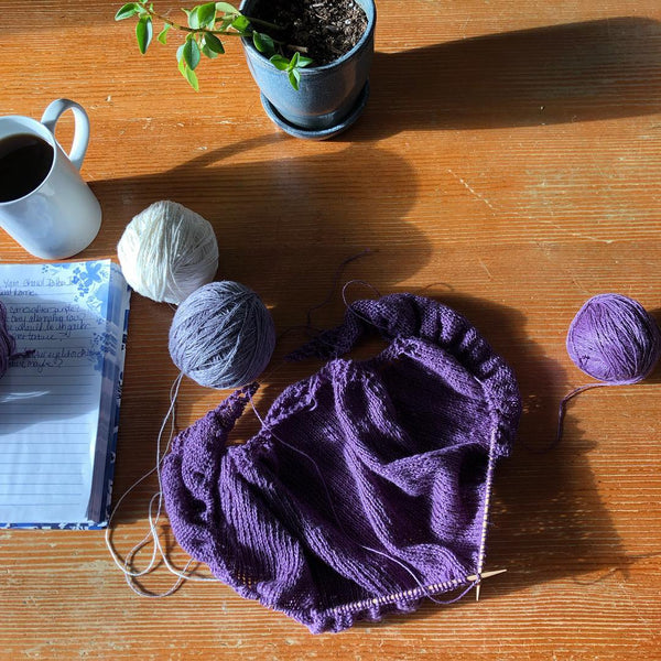Knitting project  with purple Sport Weight Yarn on a wooden surface next to notebook and coffee mug