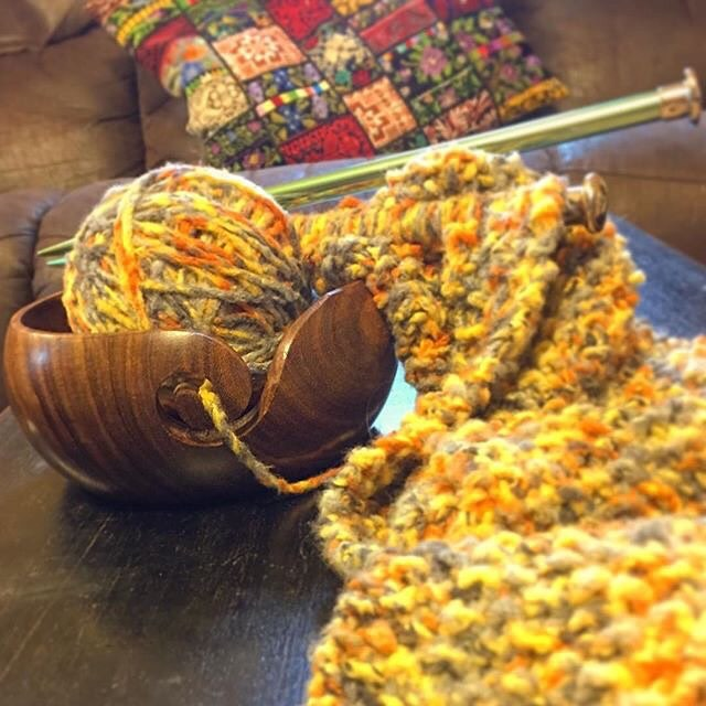 Handmade wooden yarn bowl holding a yellow ball of yarn, sitting next to a matching yellow knitting project and green aluminum knitting needles, sitting on a wooden table in front of a beige couch