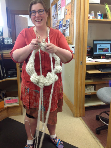 Woman wearing a pink cardigan and skirt, standing in the middle of an office space knitting a large white knitting project