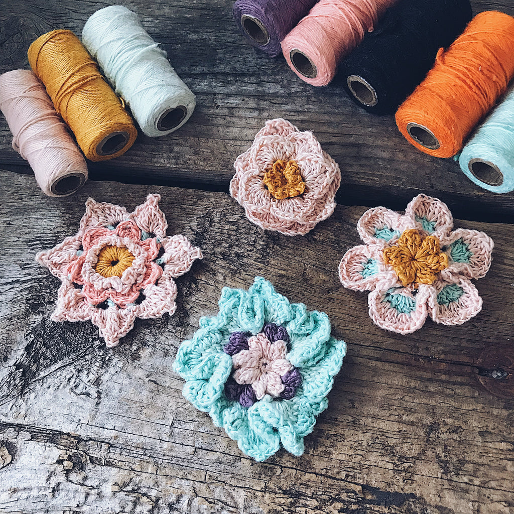 Crocheted Flower Bobbins on a wooden background