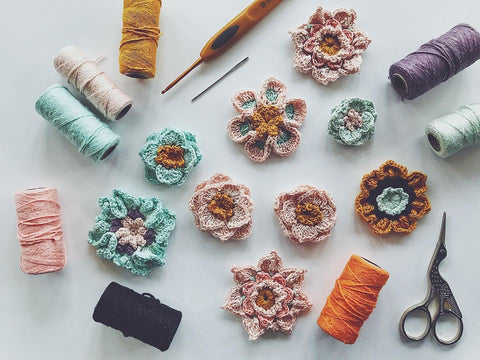 9 crocheted flowers sitting on a white surface with multiple spools of colorful yarn, stork embroidery scissors, and crochet hooks