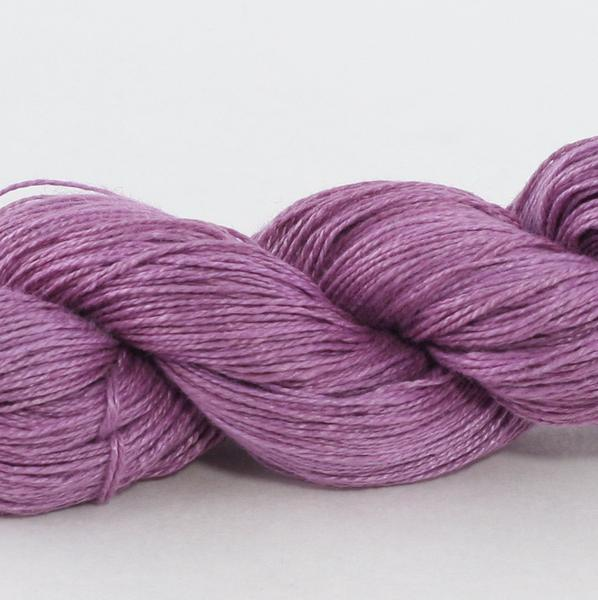 Closeup of a purple skein of linen yarn on a white background