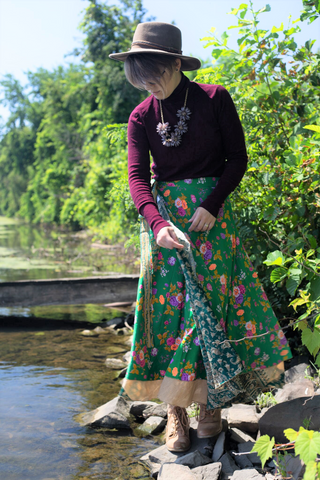 Woman wearing a sari wrap skirt and red turtleneck and hat standing in front of a body of water