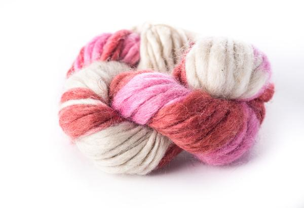pink and white skein of wool yarn on a white background