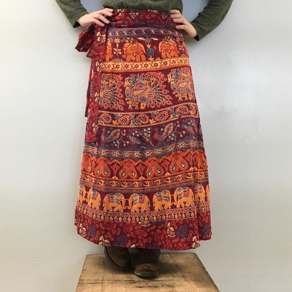 Woman standing on a wooden box wearing a maroon and orange patterned cotton maxi skirt, all in front of a white background