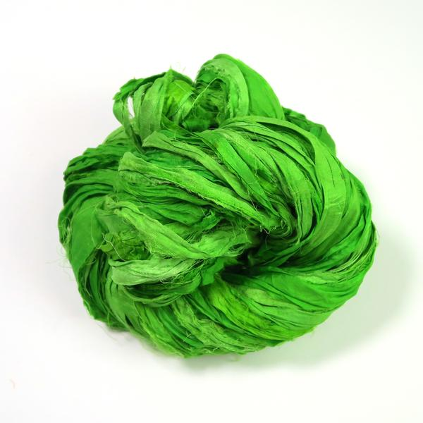 Green ball of sari silk ribbon yarn on a white background