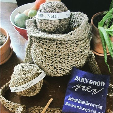 Tan nettle crochet basket holding two balls of nettle yarn, sitting next to 3 potted houseplants and a purple Darn Good Yarn flyer all on a wooden surface