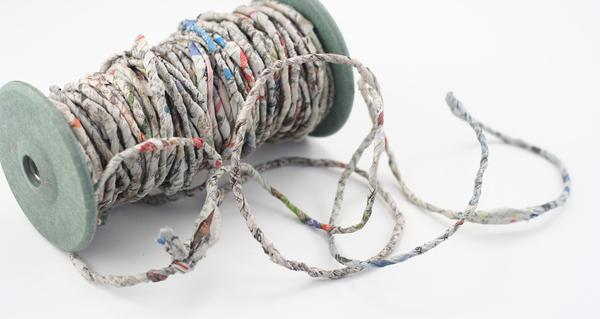 Large spool of newspaper yarn sitting on a white background