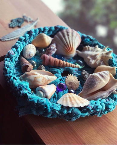 Blue knit tray holding multiple seashells and sitting on a wooden surface