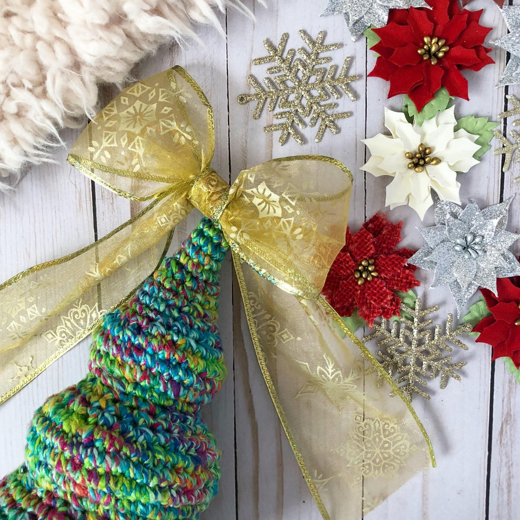 Blue and green crochet Christmas Tree with a gold bow on top sitting on a wooden surface next to faux poinsettia flowers, snowflakes, and a fur blanket